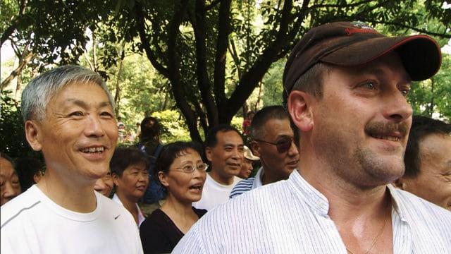 Eine europäischer Mann mit einer Gruppe Chinesen.