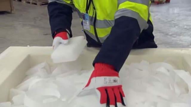 Hände mit Handschuhen fassen Eisblöcke an.