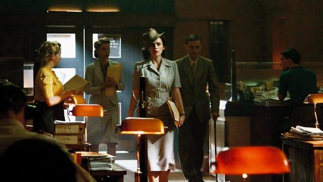 Eine Frau mit Hut steht in der Mitte einer Bar. Hinter ihr stehen zwei Frauen und ein Mann mit Gehstock.