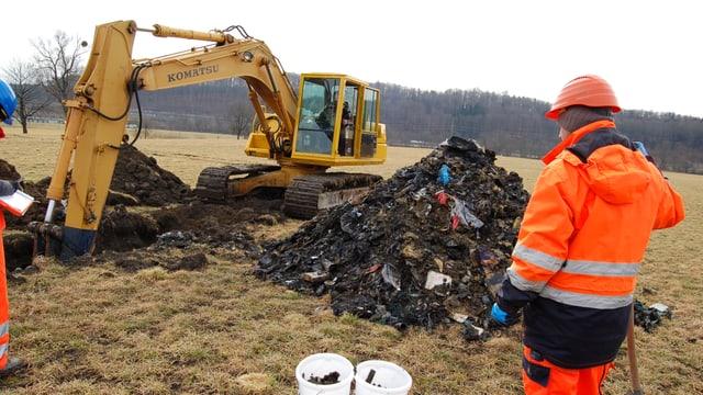 Ein Bagger gräbt ein Loch. Arbeiter sehen zu.