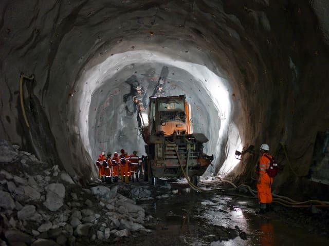 Eine Maschine und ein paar Mineure im Tunnel.