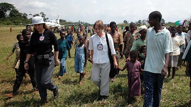 IKRK-Mitarbeiter laufen gemeinsam mit afrikanischen Menschen über einen Wald-Landeplatz.