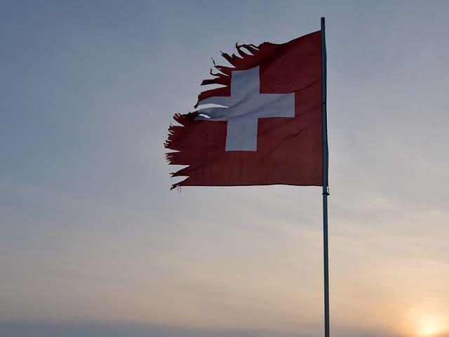 Eine zerissene Schweizer Fahne im Wind.