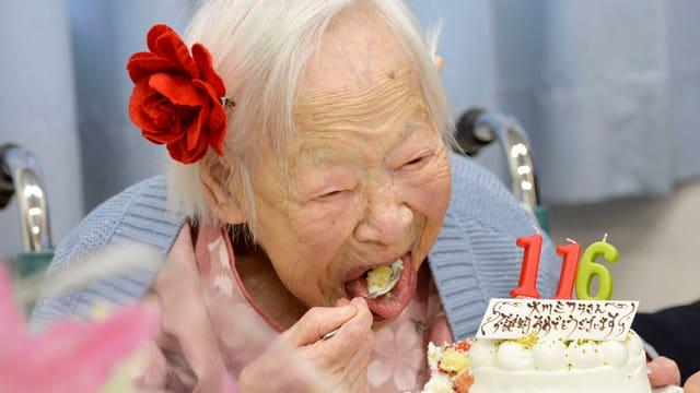 Ein ältere Dame beim Kuchen naschen