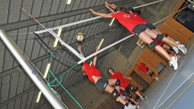 Hochspringende Frauen in roten Volleyball-Trikots am Netz