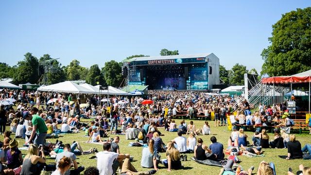 Blick auf die Hauptbühne am Gurtenfestival, Festivalgänger sitzen am Boden