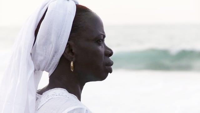 Ken Bugul trägt ein weisses Kopftuch, steht am Meer und blickt in die Ferne.