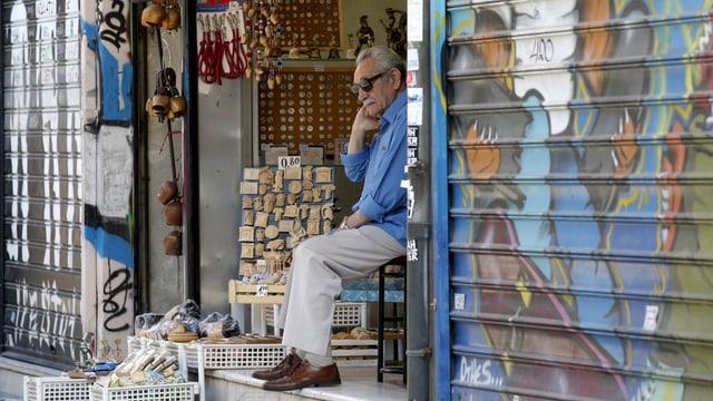 Ein Verkäufer sitzt in seinem Laden auf einem Stuhl.