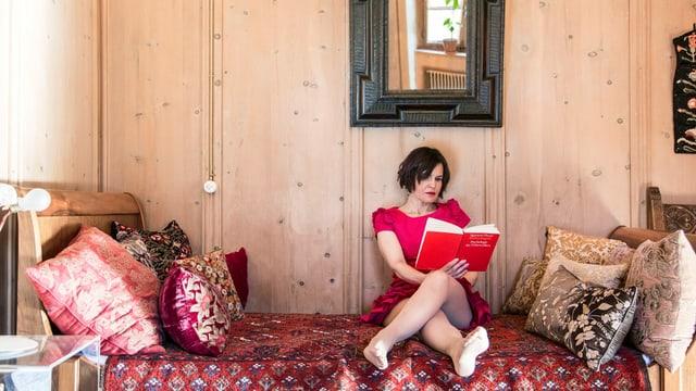 Romana Ganzoni sitzt auf dem Bett und liest