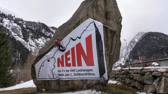 Ein Mann montiert ein Plakat gegen die zweite Gotthard-Röhre ab
