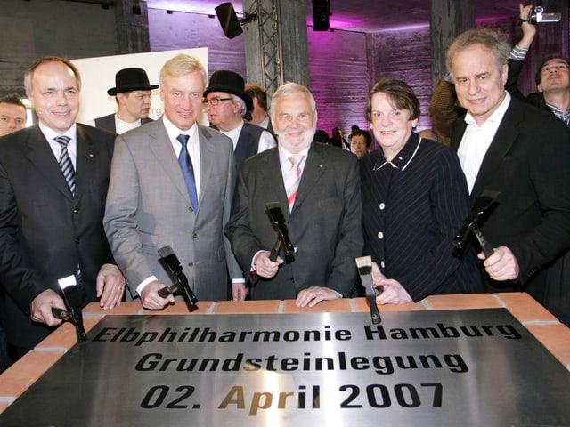 Fünf Personen mit Meissel hinter dem Grundstein der Elbphilharmonie.