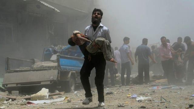 Ein Mann trägt ein verletztes Kind