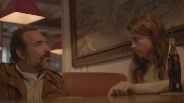 Ein Mann und eine Frau sitzen am Tisch und starren sich an.