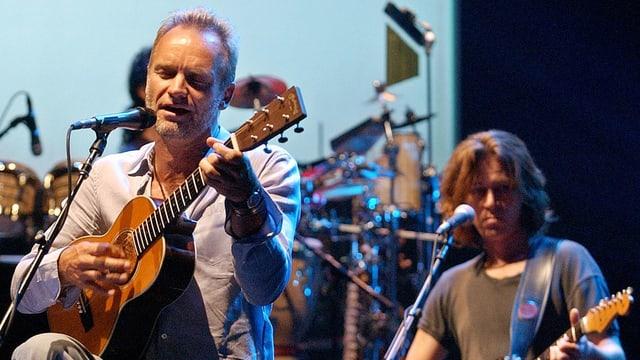 Der britische Popstar Sting auf der Bühne, im Hintergrund sein Gitarrist.