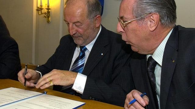 Zwei Männer unterschreiben Dokument.