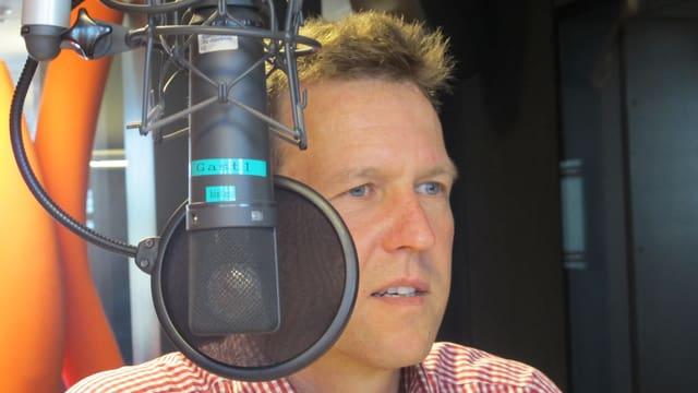 Ein Radiomikrofon, dahinter Rene Estermann mit kurzen, dunkalblonden Haaren.