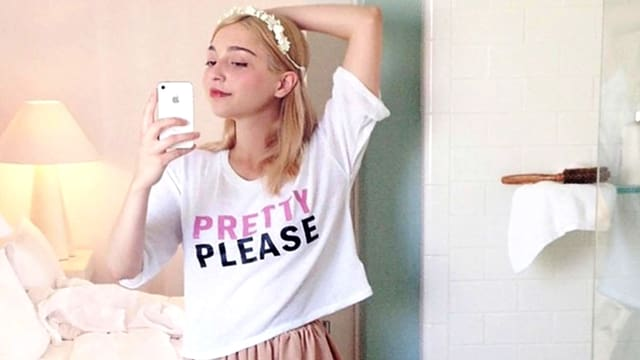 Eine junge Frau steht mir ihrem Handy vor dem Spiegel.