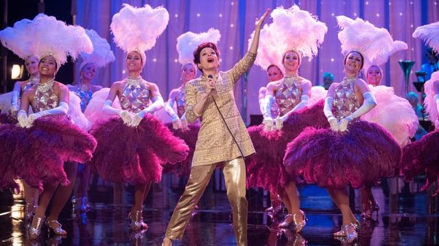 Judy steht in einem goldenen Anzug mit vielen pink angezogenen Tänzerinnen auf der Bühne.