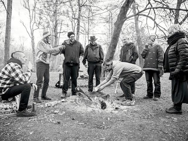 Schwarzweissbild von 7 Menschen, die in einem Wald um eine Feuerstelle stehen.
