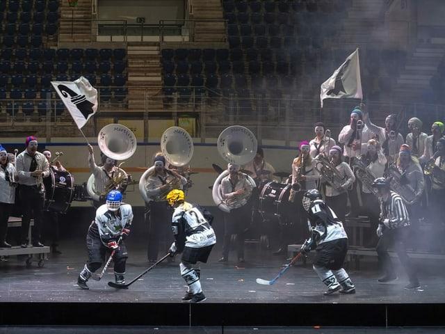 Im Hintergrund spielt eine Guggenmusik, davor Spieler eines Eishockey Clubs Eishockey.