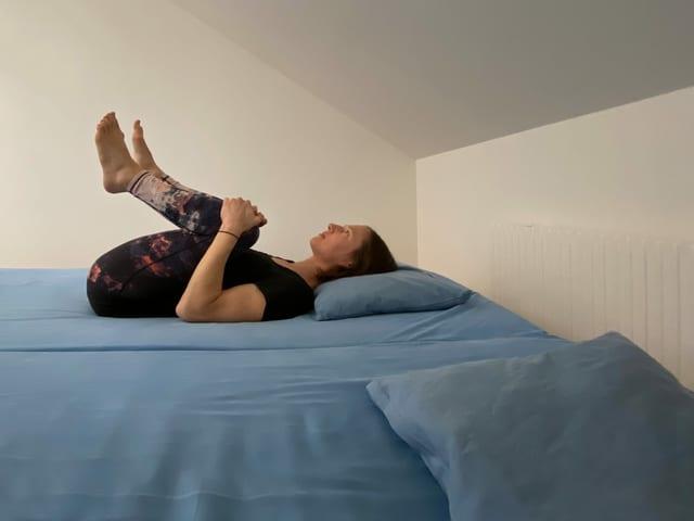 Frau liegt auf Bett und zieht Knie zur Brust.
