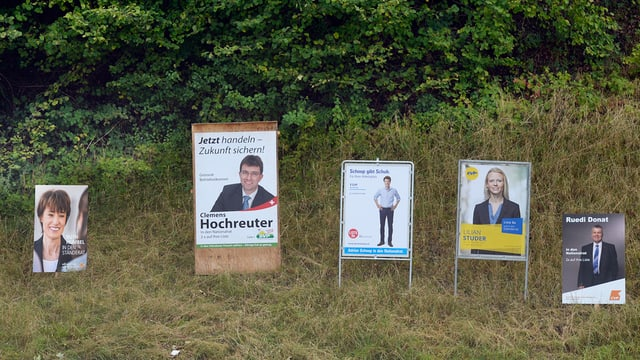 Wahlplakate verschiedener Parteien an einem Waldrand im Aargau