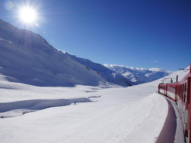 Blick aus dem Zug über eine verschneite Berglandschaft. Die Sonne scheint vom blauen Himmel.