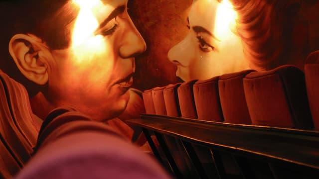 Gemälde in einem Kinosaal von einem Paar kurz vor dem Kuss.