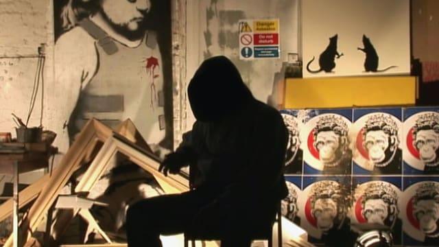Banksy sitzt in seinem Atelier, Spraykunst im Hintergrund. Er selber ist nur als schwarzer Umriss erkennbar.