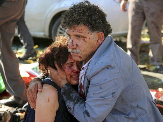 Ein verwundetes Paar liegt sich in den Armen.