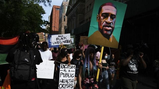 Protestierende halten ein Plakat mit einer Zeichnung von Floyd.