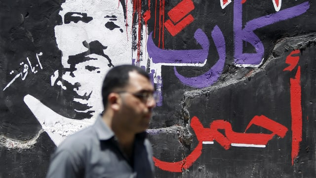 Wandgemälde mit arabischer Schrift und einem Bild von Präsident Mursi. Im Vordergrund ein Mann.