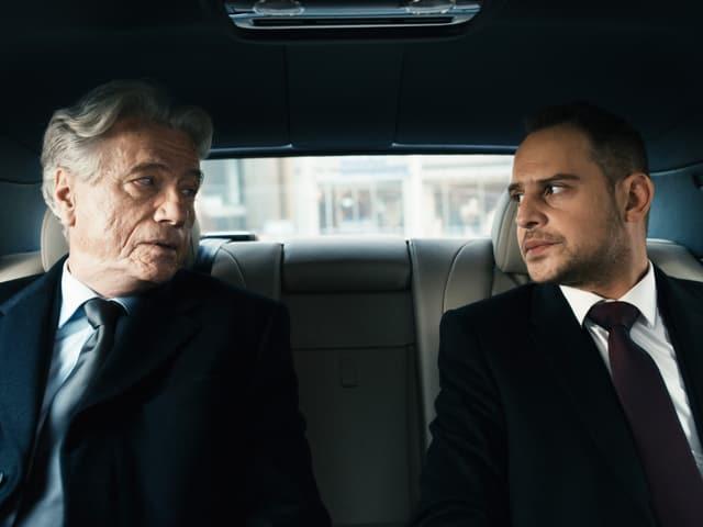 Ein jüngerer Mann und ein älterer Mann sitzen im Auto nebeneinander und schauen sich gegenseitig an.