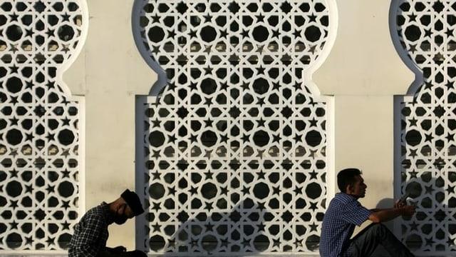 Muslime beten vor einer Wand voller Ornamente
