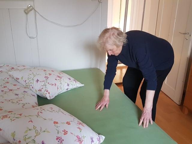 Frau macht ein Bett zurecht