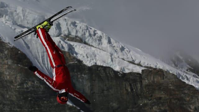 Mann in rotem Anzug mit den Ski in den Luft.