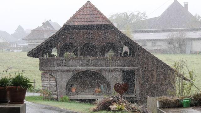 Schneeflocken vor einem Bauernhaus in Sumiswald.