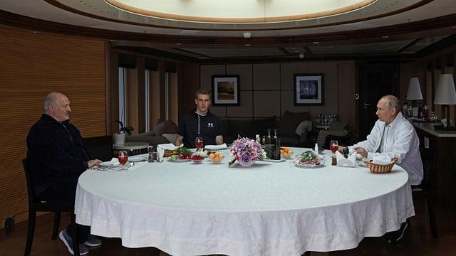 Lukaschenko, Nikolai und Putin an einem runden, weiss gedeckten Tisch.