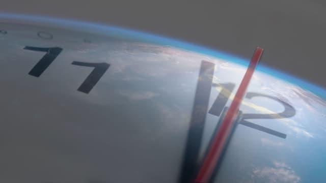 Eins vor zwölf und 59 Sekunden zeigen die Uhrzeiger auf dem Hintergrund der Erdkugel (Kollage).