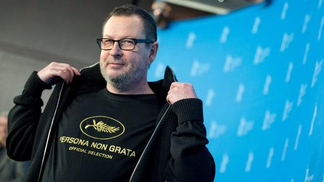 Ein Mann in schwarzer Jacke vor blauem Hintergrund.