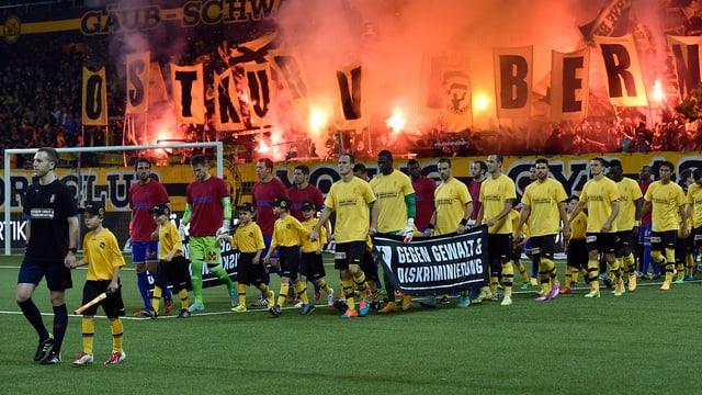 Fussballteams marschienen im Stadion ein.
