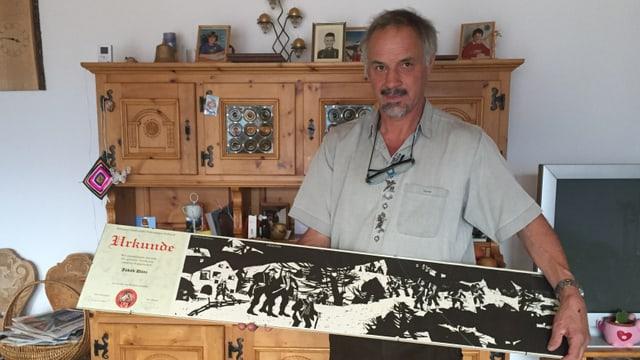 Il maletg mussa Jakob Dönz cun sia distincziun per merits spezials da l'Uniun grischuna da chatschadurs