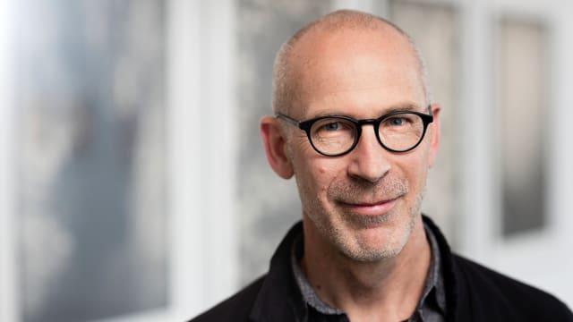 Peter Pfrunder, Direktor der Fotostiftung Schweiz: ein Mann mit Glatze und schwarzer Brille.