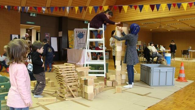 Kinder bauen mit Holzklötzen einen Turm. Ein Kind auf Leiter.