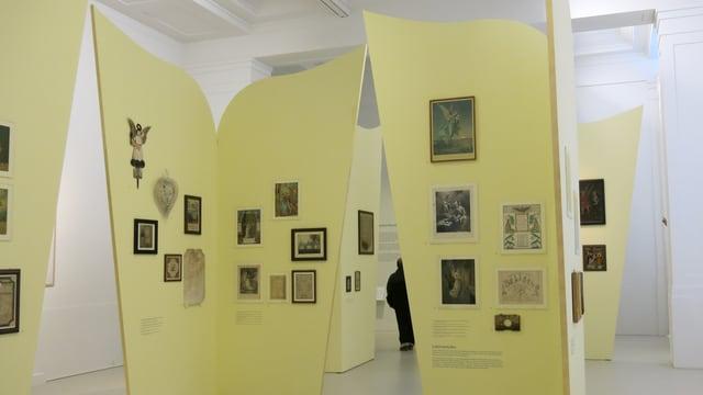 An Stellwänden in Form von Engelsflügeln hängen viele Engelsbilder.