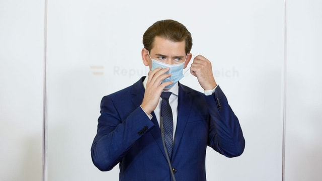 purtret da Sebastian Kurz che metta gist si ina mascra da protecziun.