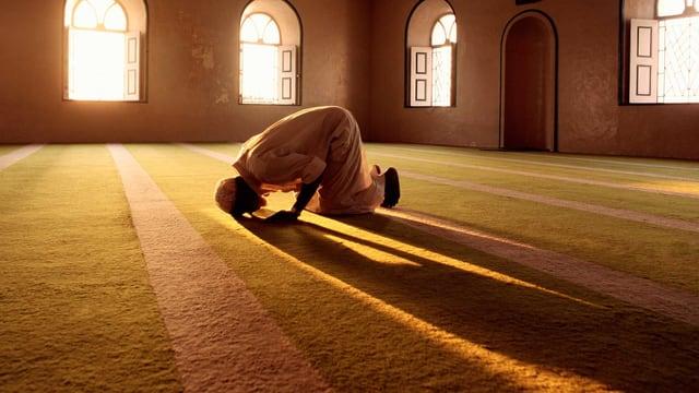 Ein Mann betet in einem gelb erleuchteten Raum.