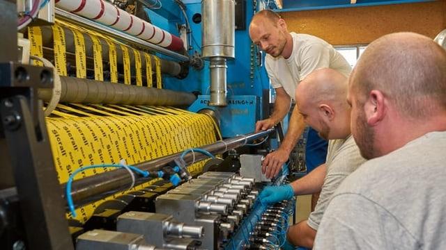 Drei Männer stehen neben einer Maschine, die Klebeband herstellt.