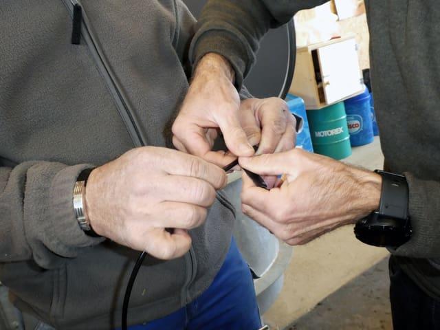 Zwei Männer halten eine Zündschnur
