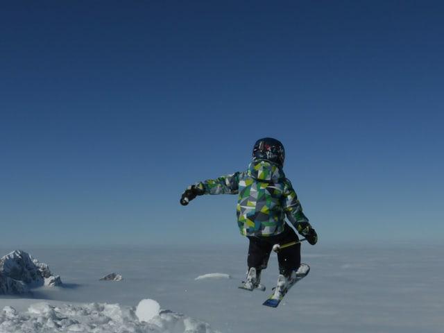 Ein Kind springt mit den Ski's. Im Hintergrund liegt ein Nebelmeer.